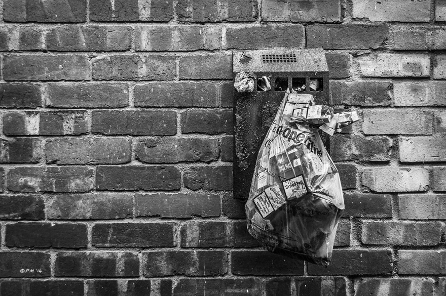 Wall mounted ash tray cigarette bin with plastic bag full of cigarette packets having from grille on brick wall. Marion Road, Hove UK. Monochrome Landscape.  © P. Maton 2014 eyeteeth.net