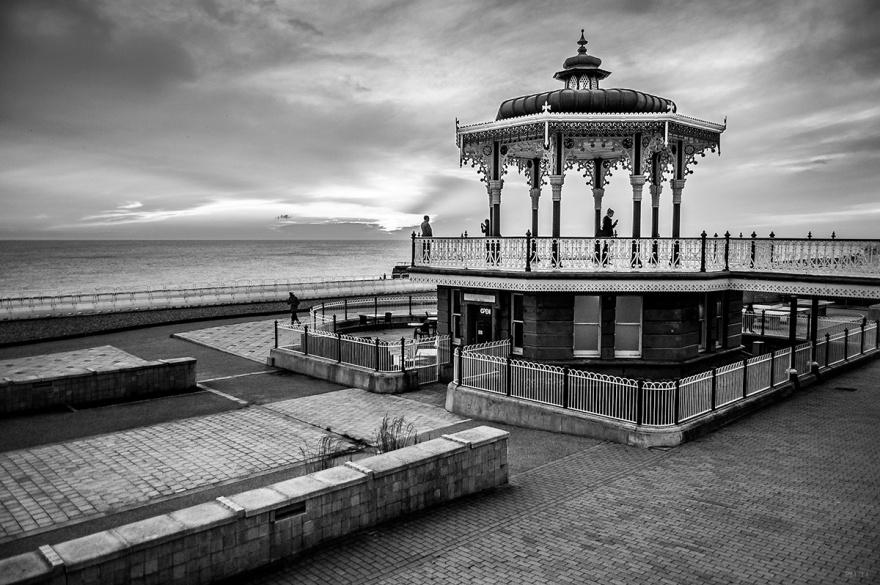 Regency Bandstand on Brighton Seafront with people taking photographs and low sun over sea in background. Brighton UK. Monochrome Landscape. © P. Maton 2014 eyeteeth.net