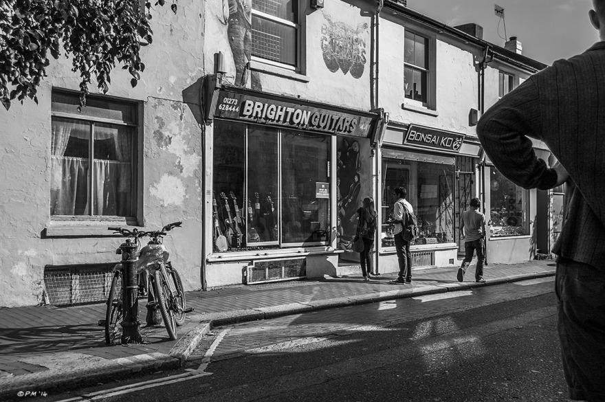 People going into Brighton Guitars shop with silhouetted figure in foreground and sunlight reflecting off windows. Sydney Street Brighton UK. Monochrome Landscape. © P. Maton 2014 eyeteeth.net