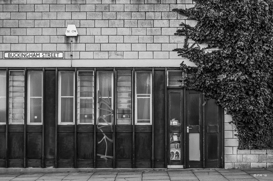 Concrete blocks, wooden door and windows with encroaching Ivy, Business building on corner of Buckingham Street, Brighton UK. Monochrome Landscape. © P. Maton 2014 eyeteeth.net