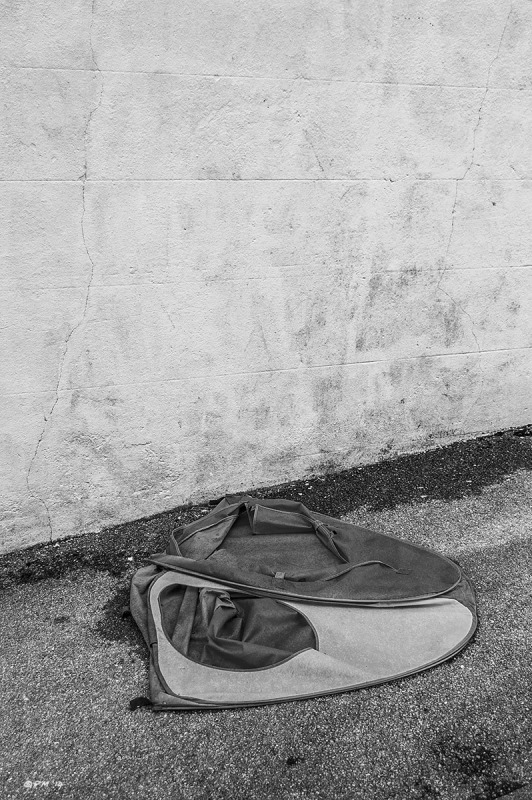 Childs tent on asphelt pavement sidewalk beside  white wall. Monochrome Portrait abstract. G P. Maton 2014 eyeteeth.net