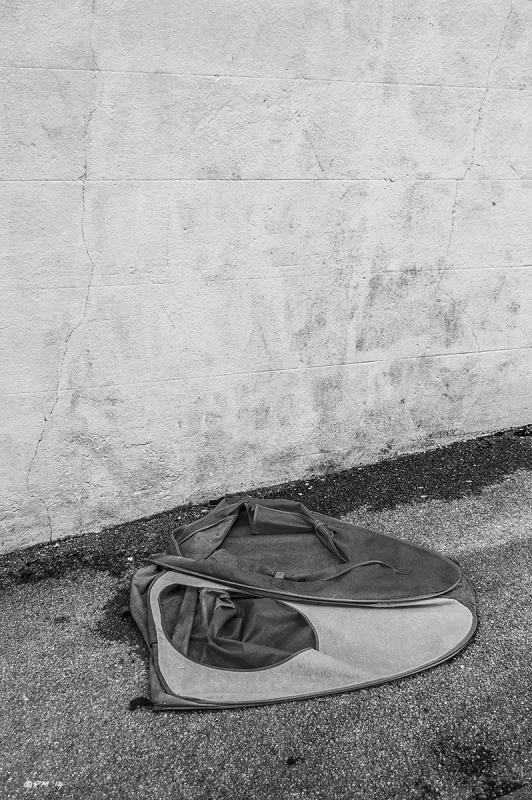 Childs tent on asphelt pavement sidewalk beside  white wall. Monochrome Portrait abstract. G P. Maton 2014 eyeteeth.net