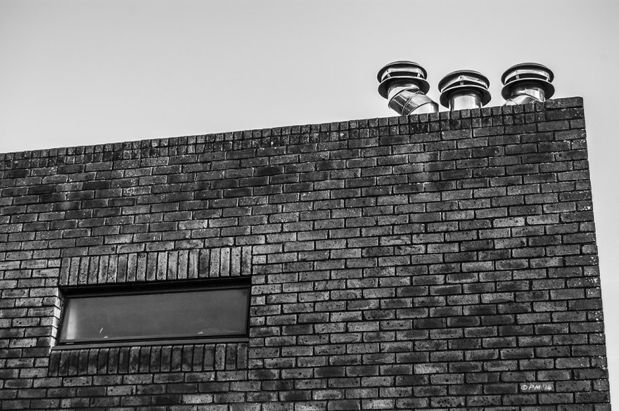Three metal chimney flus on top of flat roofed brick building with single pane window. Rutland Gardens Hove UK. Monochrome Landscape. © P. Maton 2014 eyeteeth.net