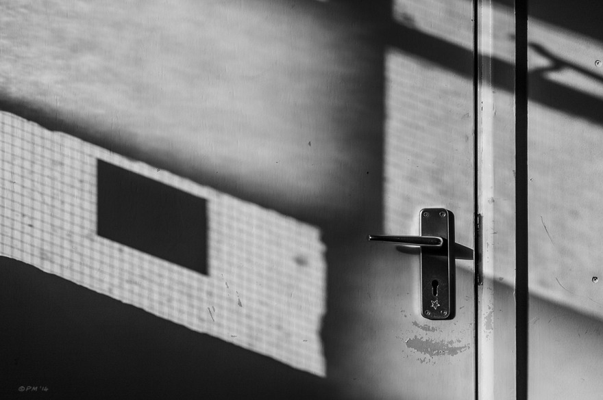 Detail of closed door showing handle with light cast through reinforced glass windows. Land port Boys Club, Lewes East Sussex. Monochrome landscape. © P. Maton 2014 eyeteeth.net