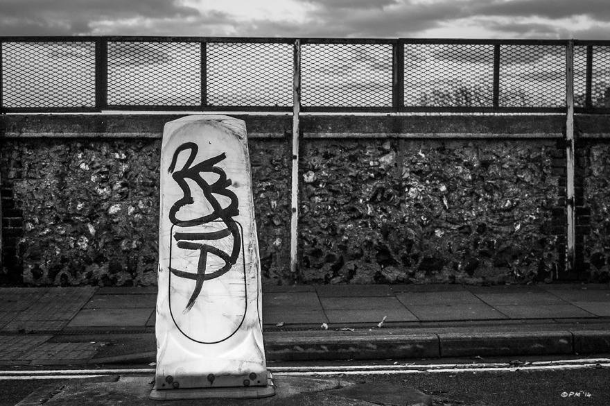 Illuminated road Bollard with graffiti  tag in road with flint railway bridge wall in background. Monochrome landscape. © P. Maton 2014 eyeteeth.net