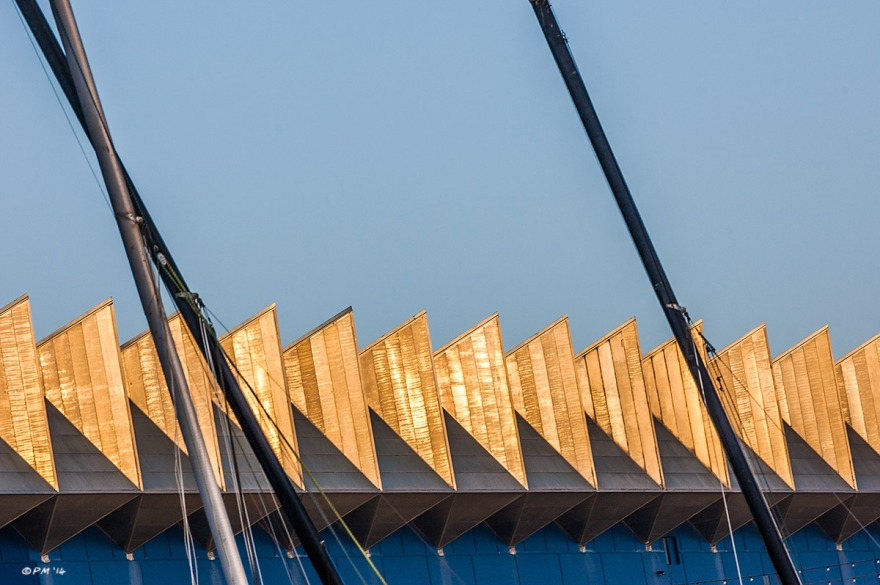 Geometric roof  of  Odeon Cinema catching golden sunlight with boat masts in foreground. Brighton UK. Abstract Colour Landscape. © P. Maton 2014 eyeteeth.net