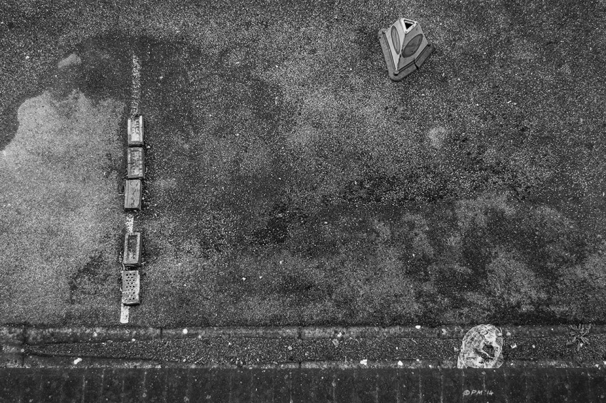 Car Park with Bricks over white line on weathered asphalt, traffic cone and discarded plastic bag seen from above. Abstract Monochrome Landscape. © P. Maton 2014 eyeteeth.net