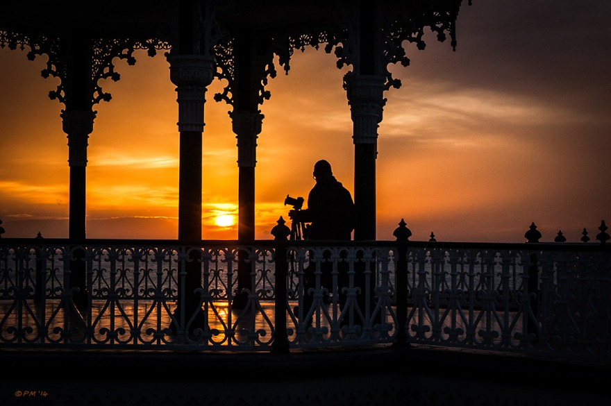 Photographer moving into position on Brighton Bandstand silhouetted by low winter sun, Brighton UK. Colour Landscape.  © P. Maton 2014 eyeteeth.net