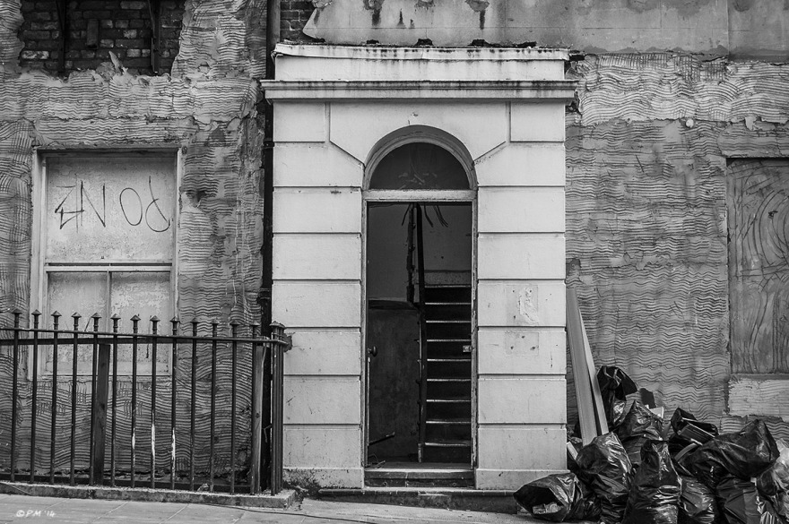 Regency town house undergoing renovation, narrow arched doorway with stairs beyond and walls stripped of render, black refuse sacks on pavement, Brighton UK. Monochrome Landscape.  © P. Maton 2014 eyeteeth.net