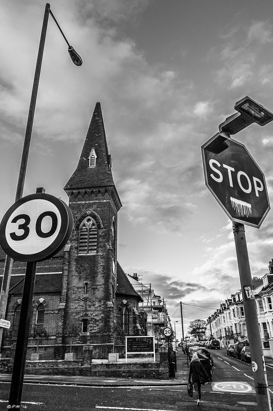 Saint Lukes Church with road signs in foreground and view down Stanford Road, Brighton UK. Monochrome Portrait. © P. Maton 2014 eyeteeth.net