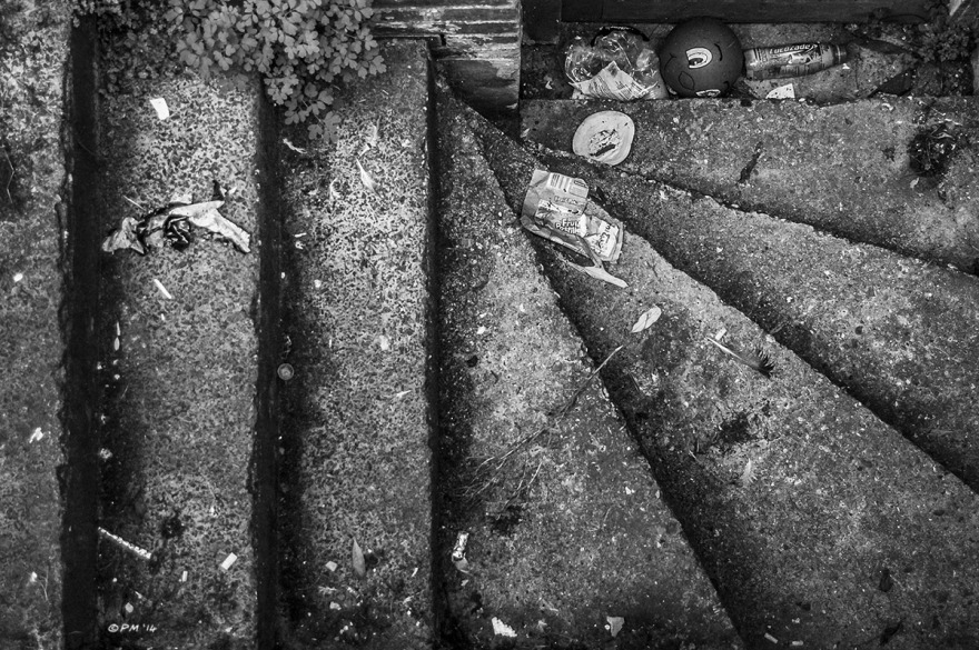 Ball with smiley face by door at bottom of stairwell , concrete steps with rubbish and detritus . Marion Road Hove UK. Monochrome Landscape. © P. Maton 2014 eyeteeth.net