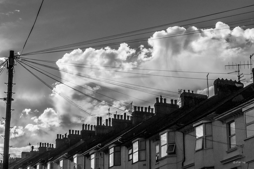 Terraced houses with silhouetted chimney pots and dramatic cloud formation. Old Shoreham Road, Brighton UK. Monochrome Landscape. © P. Maton 2014 eyeteeth.net