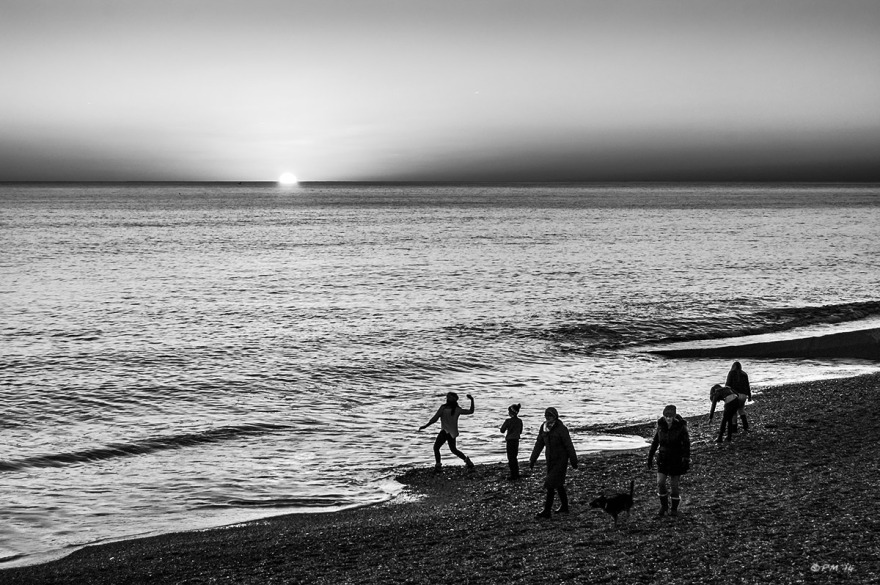 Girl throwing pebbles into the sea with friends at sunset, people walking dog, sun disappearing over horizon. Hove seafront UK. Monochrome Landscape. © P. Maton 2014 eyeteeth.net