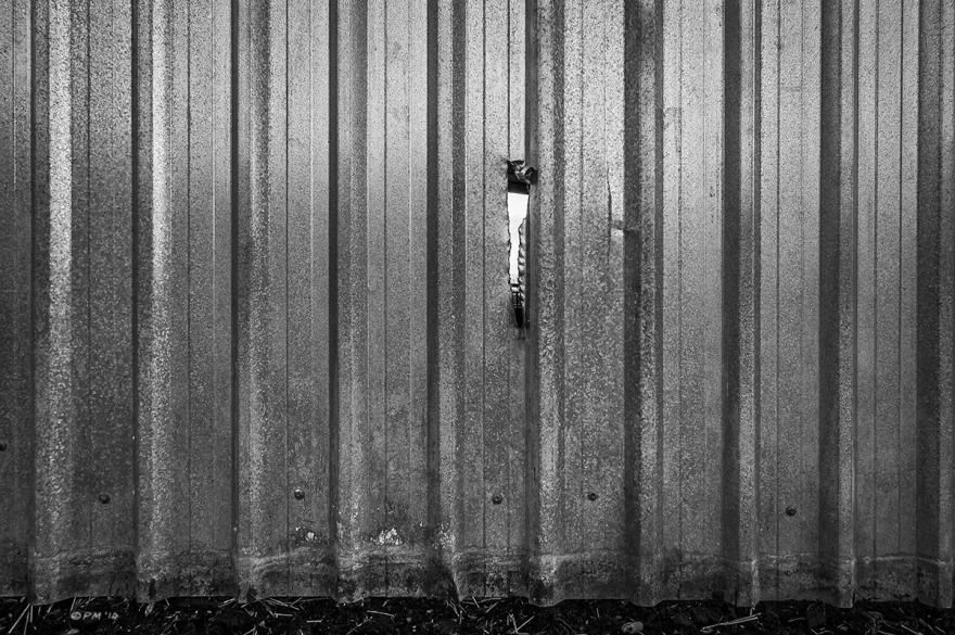 Hole torn in corrugated galvanised steel barn wall, Mohair Centre, East Sussex UK. Monochrome Landscape. © P. Maton 2014 eyeteeth.net