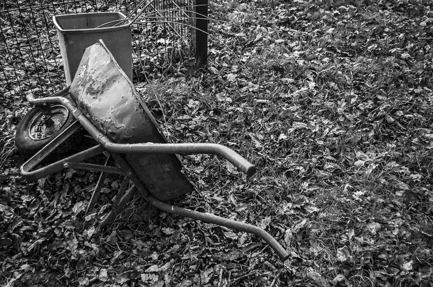 Old wheelbarrow lying on side next to plastic bin on grass strewn with dead leavesMohair Centre Sussex UK. Monochrome Landscape. © P. Maton 2014 eyeteeth.net