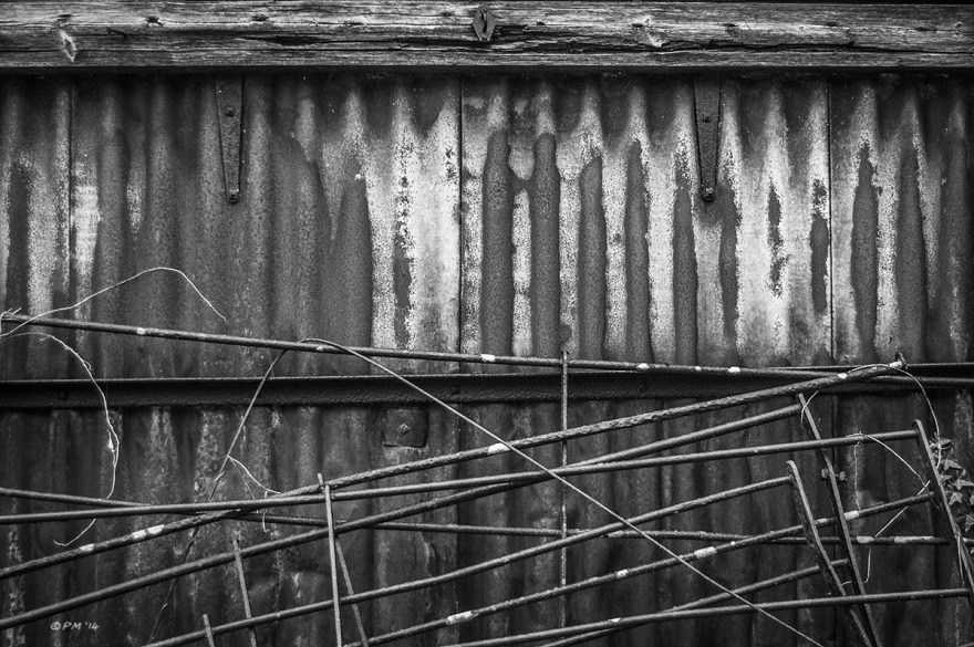Rusty corrugated iron shed wall with iron fencing . Ford Lane, Frilford Oxfordshire UK. Monochrome Landscape. © P. Maton 2014 eyeteeth.net