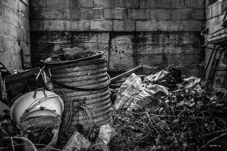 Corrugated Barrel and plastic sacks among detritus in abandoned stable. Ford Lane, Frilford Oxfordshire UK. Monochrome Landscape. © P. Maton 2014 eyeteeth.net
