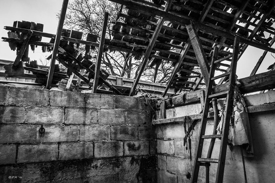 Interior with Ladder and scythe decayed walls and collapsing roof with wooden tiles abandoned stable. Ford Lane, Frilford Oxfordshire UK. Monochrome Landscape. © P. Maton 2014 eyeteeth.net