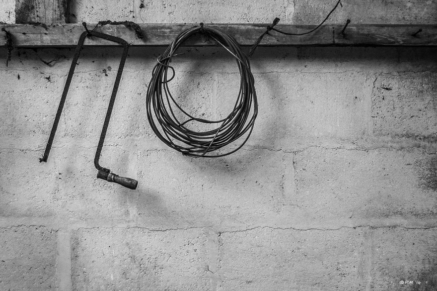 Coping saw and coiled cable hanging on beam in abandoned stable. Ford Lane, Frilford Oxfordshire UK. Monochrome Landscape. © P. Maton 2014 eyeteeth.net