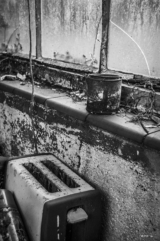 Old toaster next to decaying window with rusty paint tin on windowsill in abandoned stable. Ford Lane, Frilford Oxfordshire UK. Monochrome Portrait. © P. Maton 2014 eyeteeth.net