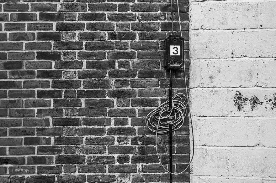 Metal electrical box with number three  and cable coil on brick wall next to white concrete block wall. Abstract. Lewes UK. Monochrome Landscape. © P. Maton 2015 eyeteeth.net