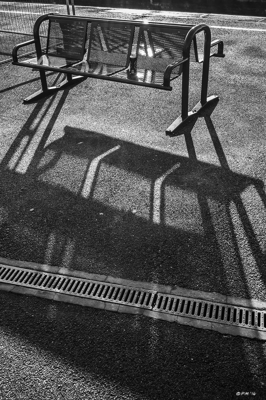 Metal bench with beer can casting long shadow towards viewer. Didcot Station, Oxfordshire UK. Monochrome  Portrait. © P. Maton 2014 eyeteeth.net