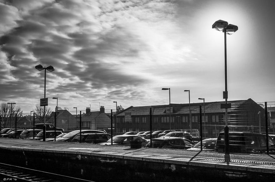 Railway station platform with overhead lamps in silhouette with parked cars and buildings in background and clouds encroaching on clear sky with sun. Didcot Station, Oxfordshire UK.  Monochrome Landscape. © P. Maton 2014 eyeteeth.net