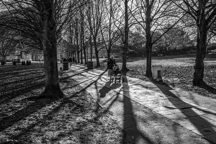Tree lined flagstone path with long shadows and woman pushing pram. Cathedral grounds, Winchester UK. Monochrome Landscape. © P. Maton 2014 eyeteeth.net