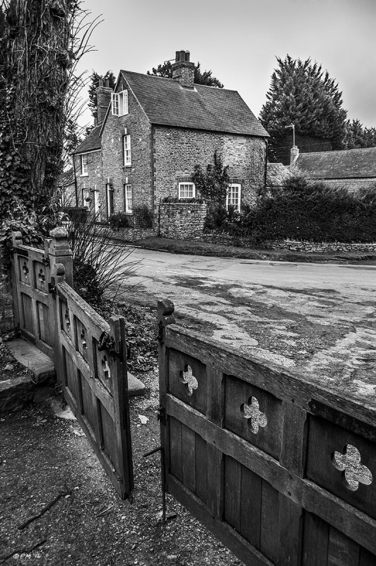 Church gates with stone cottage in background. Church Street, Marcham Oxfordshire UK. Monochrome Portrait. © P. Maton 2014 eyeteeth.net