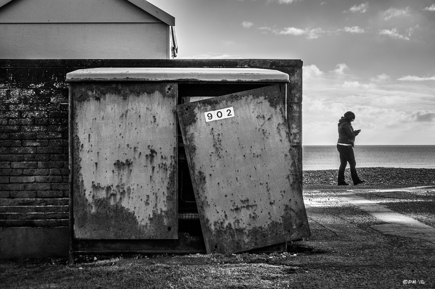 Telephone exchange box with door having off with beach hut and person on mobile phone walking along seafront, Hove UK. Monochrome Landscape.© P. Maton 2015 eyeteeth.net