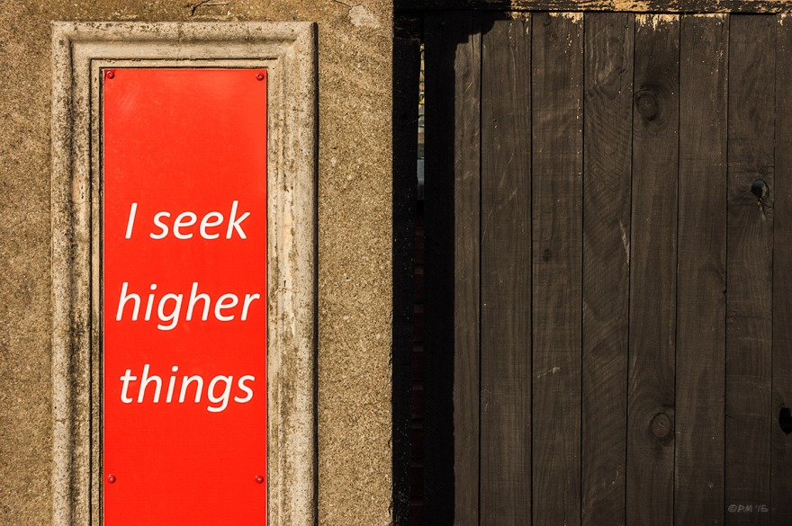 Red sign saying 'I Seek Higher Things' on stone gate post with black wooden fence.  New Church Road, Hove UK. Colour Landscape.© P. Maton 2015 eyeteeth.net