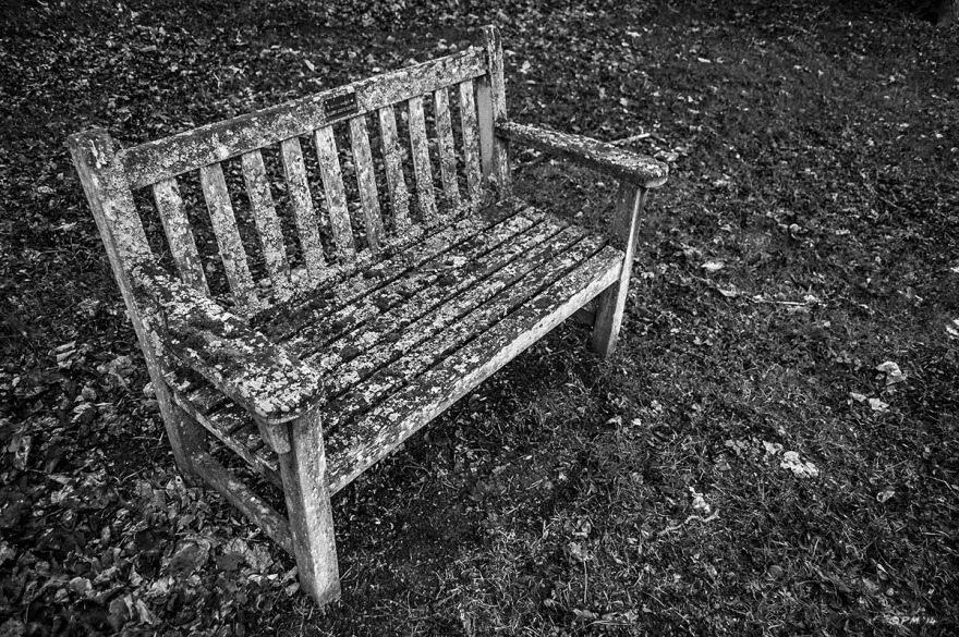 Wooden bench covered in Lichen sitting on graveyard lawn. All Saints Graveyard Macham Oxfordshire UK. Monochrome Landscape. © P. Maton 2014 eyeteeth.net