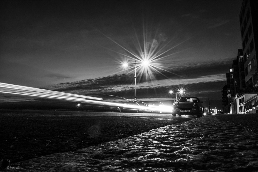 Streaks of light from passing cars with flare from street lamps , parked car and waining sunset. Kingsway Hove UK. Monochrome Landscape. © P. Maton 2015 eyeteeth.net