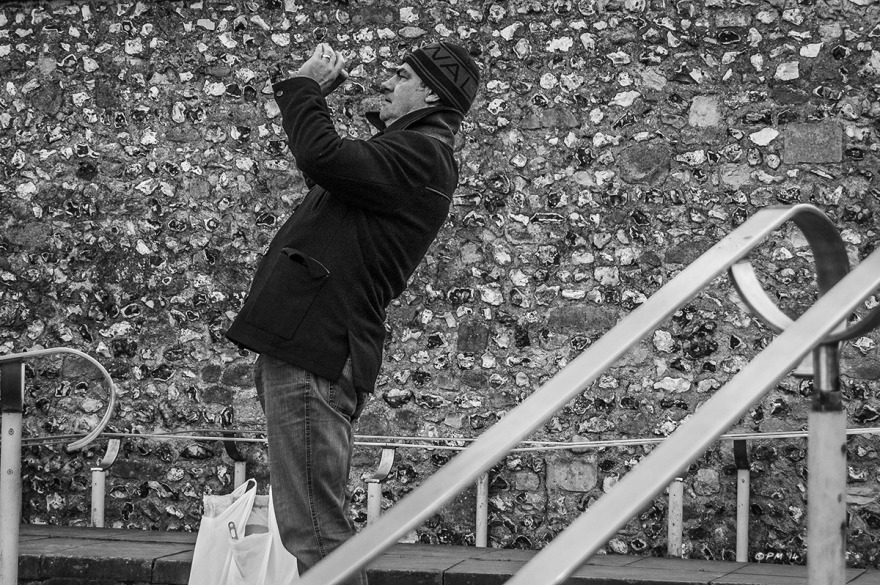 Man leaning back taking picture with phone against snapped flint wall. Winchester Cathedral UK. Monochrome Landscape. © P. Maton 2014 eyeteeth.net