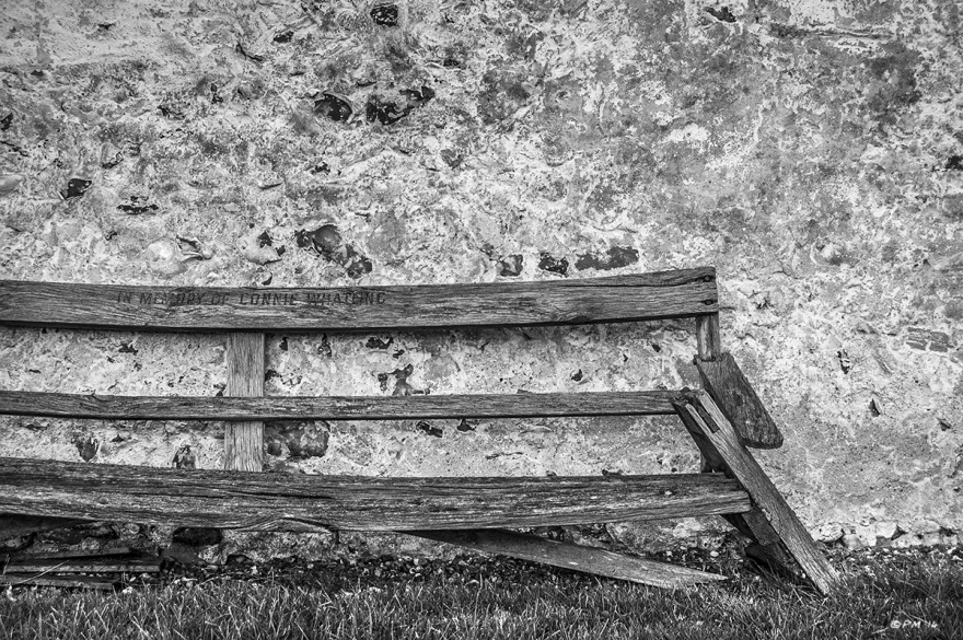 Collapsing wooden memorial bench by flint wall. St Mary The Virgin Church Silchester Berkshire UK. Monochrome Landscape. © P. Maton 2014 eyeteeth.net