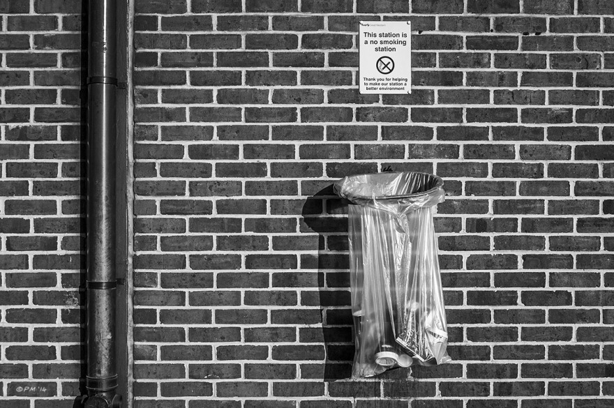 Brick wall with drain pipe, Waste bin and no smoking sign. Didcot Station, Oxfordshire UK. Monochrome Landscape. © P. Maton 2014 eyeteeth.net