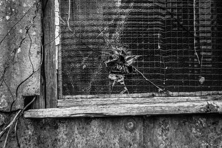 Bullet hole in reinforced glass window abandoned shed. Ford Lane, Frilford Oxfordshire UK. Monochrome Landscape. © P. Maton 2014 eyeteeth.net