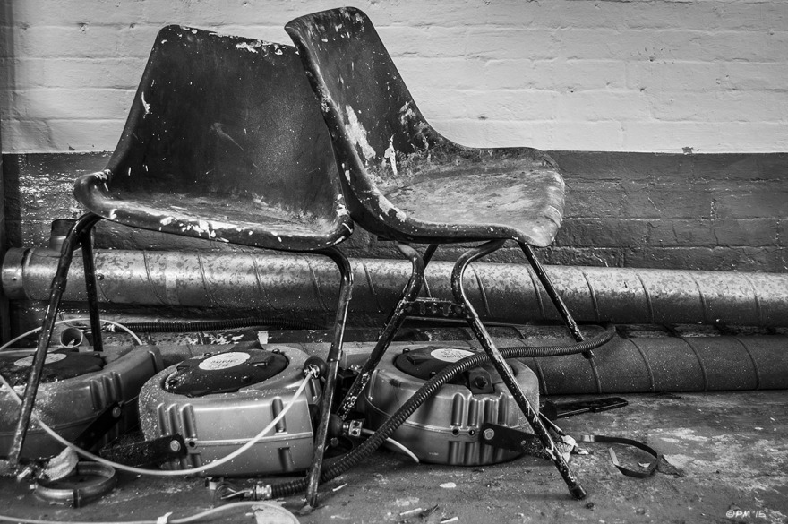 Plastic chairs with paint marks place over plastic devices with metal flue and painted wall in background. Bexhill On Sea, Sussex UK. Monochrome Landscape. © P. Maton 2015 eyeteeth.net