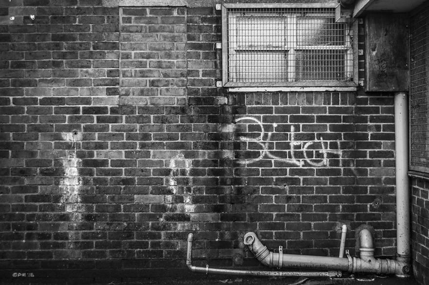 'Bitch' graffiti on Grimy wall with mesh covered window, bricked up window and pipe work. Land Port Boys Club, Lewes, East Sussex UK. Monochrome Landscape. © P. Maton 2015 eyeteeth.net