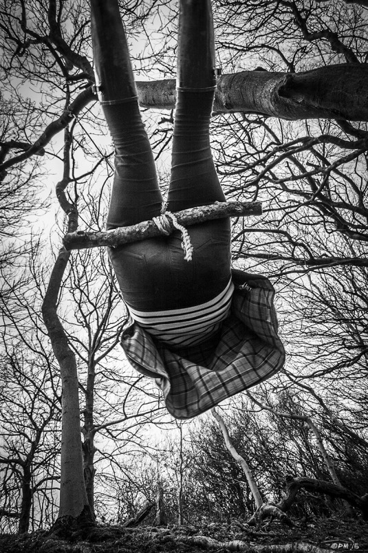 Woman on rope swing with legs in the air and trees in the sky.  Chanctonbury Ring Hill, West Sussex UK. Monochrome Portrait. © P. Maton 2015 eyeteeth.net