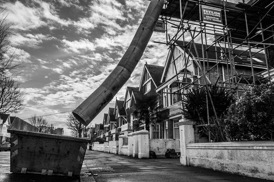 Rubbish Chute hanging off scaffolding over pavement leading to skip with row of houses and clouds in sky. Carlisle Road Hove UK. Monochrome Landscape. © P. Maton 2015 eyeteeth.net