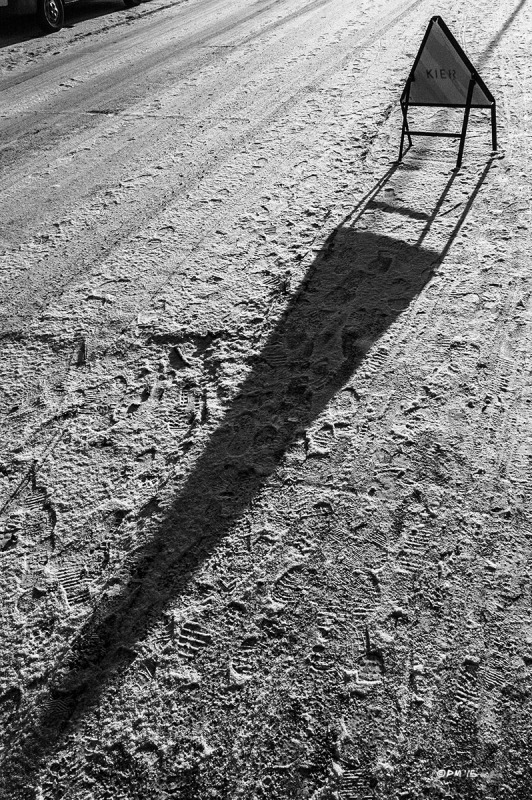 Warning sign stands on snow covered road casting long shadow. Landport, Lewes, East Sussex UK. Monochrome Landscape. © P. Maton 2015 eyeteeth.net