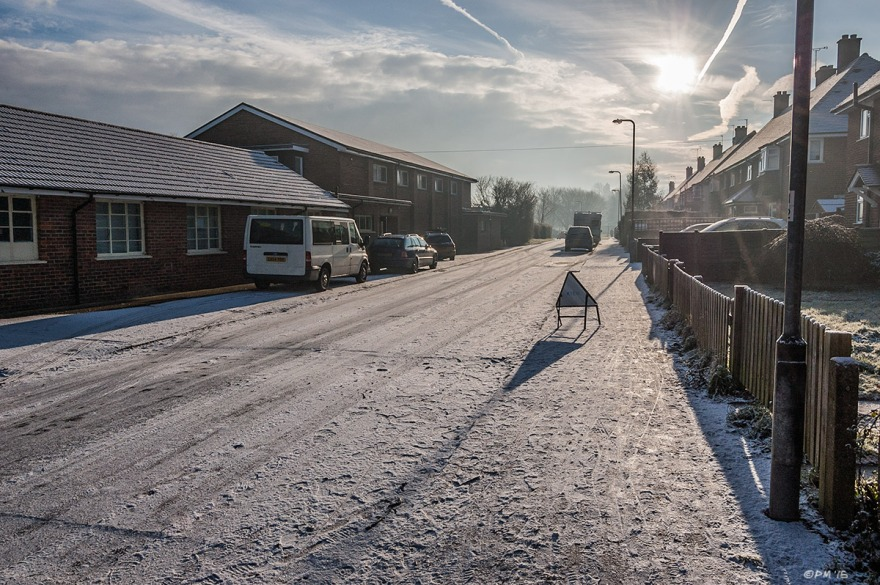 Snow covered street with footprints, warning sign , row of semi-detached houses and youth club building lit by morning sun shining through haze. Land port Lewes UK. Colour Landscape. © P. Maton 2015 eyeteeth.net