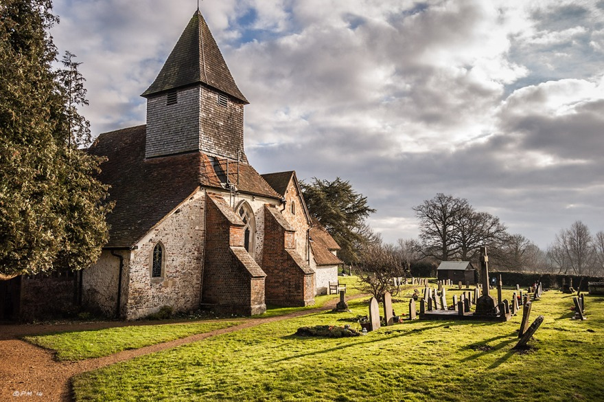 Church with tiled square spire with sunlit gravestones casting long shadow across grass, dramatic sky. St Mary The Virgin Church Silchester Berkshire UK. Colour Landscape. © P. Maton  2014 eyeteeth.net