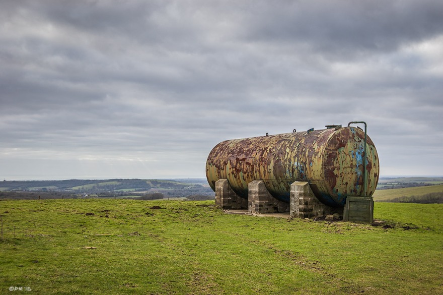 Rusty Water Tank standing with concrete piles on grassland hill with view to sea and overcast cloudy sky. Chanctonbury Ring Hill, West Sussex UK. Colour Landscape. © P. Maton 2015 eyeteeth.net