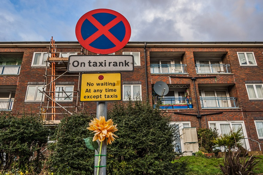 Taxi Rank sign with yellow plastic flower attached to post in front of flats. Portland Road, Hove UK. Colour Landscape. © P. Maton 2015 eyeteeth.net