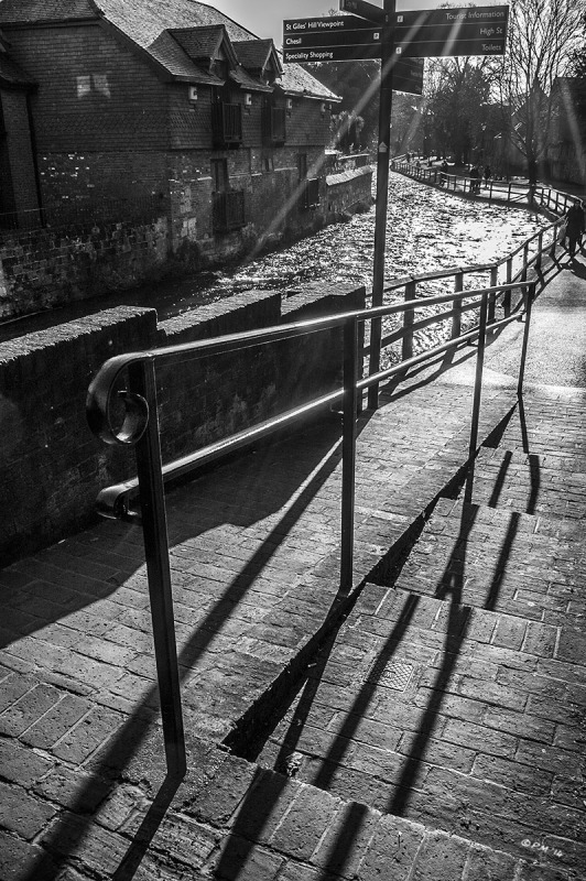 The Weirs walkway beside the river Itchen with sun flare and long shadows of railings, Winchester UK. Monochrome Portrait. © P. Maton 2014 eyeteeth.net