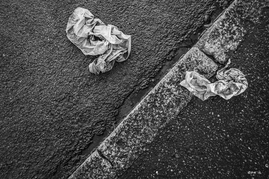 Two paper towels lying on wet road and pavement / sidewalk with curb stones. New Church Road, Hove UK. Monochrome Landscape.© P. Maton 2015 eyeteeth.net