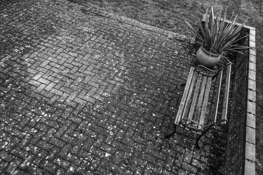 Bench on patio with mark left by absent table. Mortimer, Berkshire UK. Monochrome Landscape. © P. Maton 2014 eyeteeth.net