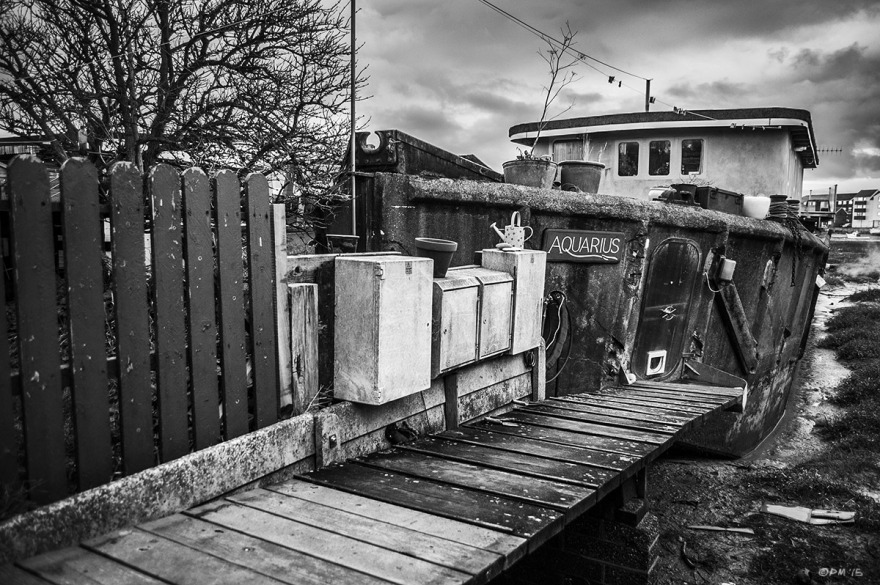 Concrete barge houseboat 'Aquarius' on gang plank moorings next to fence with electrical boxes.  River Adur Shoreham Harbour UK. Monochrome Landscape. © P. Maton 2015 eyeteeth.net